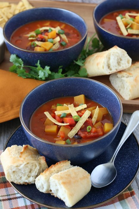 A serving of butternut squash chili in a bowl with a spoon and some bread, ready to be enjoyed.