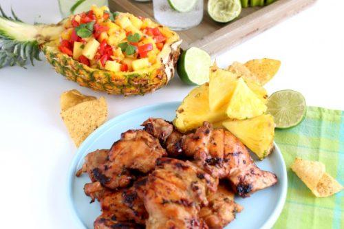 Poulet mariné grillé servi avec de l'eau pétillante et une sauce aux ananas.