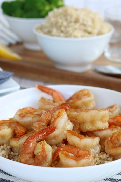 Beautiful shot of the final product of how to cook shrimp. The honey garlic shrimp are on top of a bowl of rice, an easy shrimp recipe ready to eat!