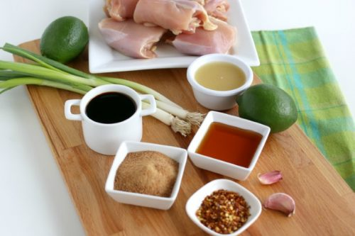 Ingredients to make a grilled chicken marinade resting on a wooden cutting board.