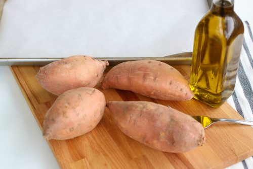 Sweet potatoes on a wood cutting board with olive oil.