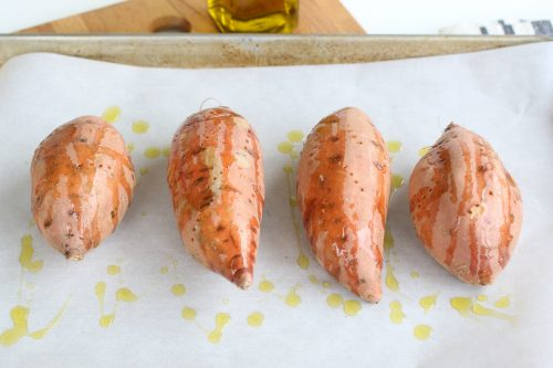Sweet potatoes covered with olive oil prior to baking.