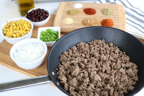 Cooked ground beef alongside mexican spices.